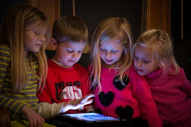 Kinder spielen mit einem Tablet