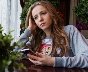 Mädchen mit Smartphone, wirkt traurig.